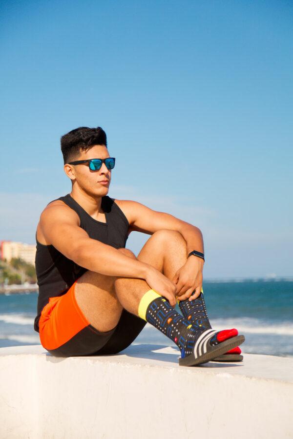 hombre en la playa con lentes de sol calcetines de pacman