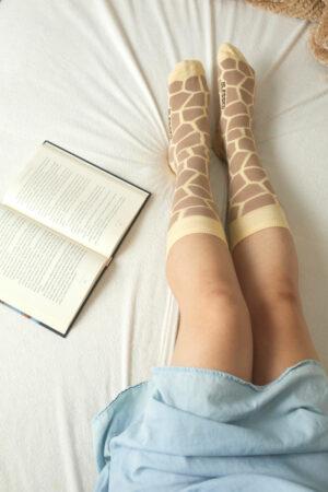 calcetines de jirafa en cama con libro abierto